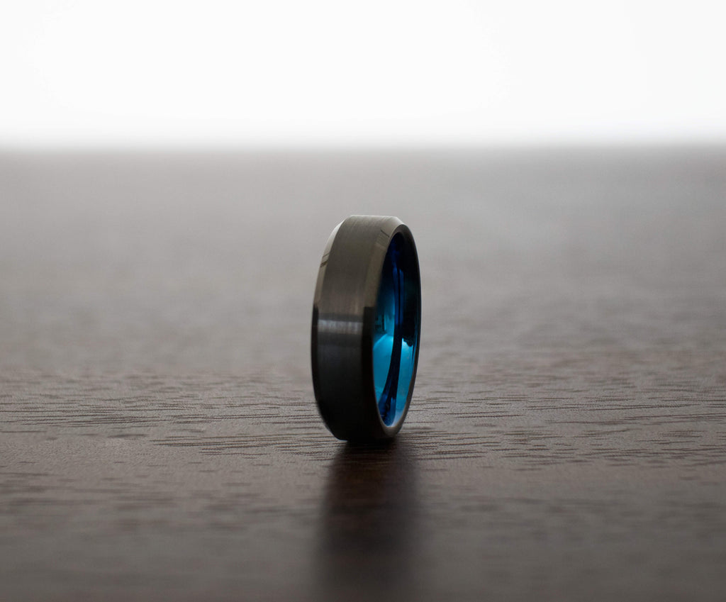 black-obsidian-blue-tungsten-mens-wedding-band-on-table-slight-angle