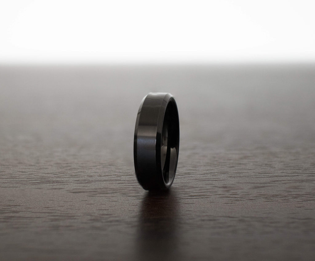 black-obsidian-sleek-tungsten-mens-wedding-band-on-table-slight-angle