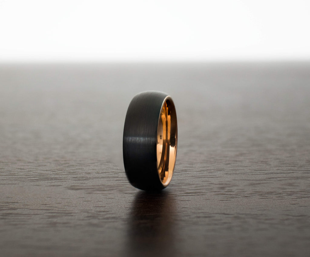 black-raven-hue-rose-gold-tungsten-mens-wedding-band-on-table-slight-angle
