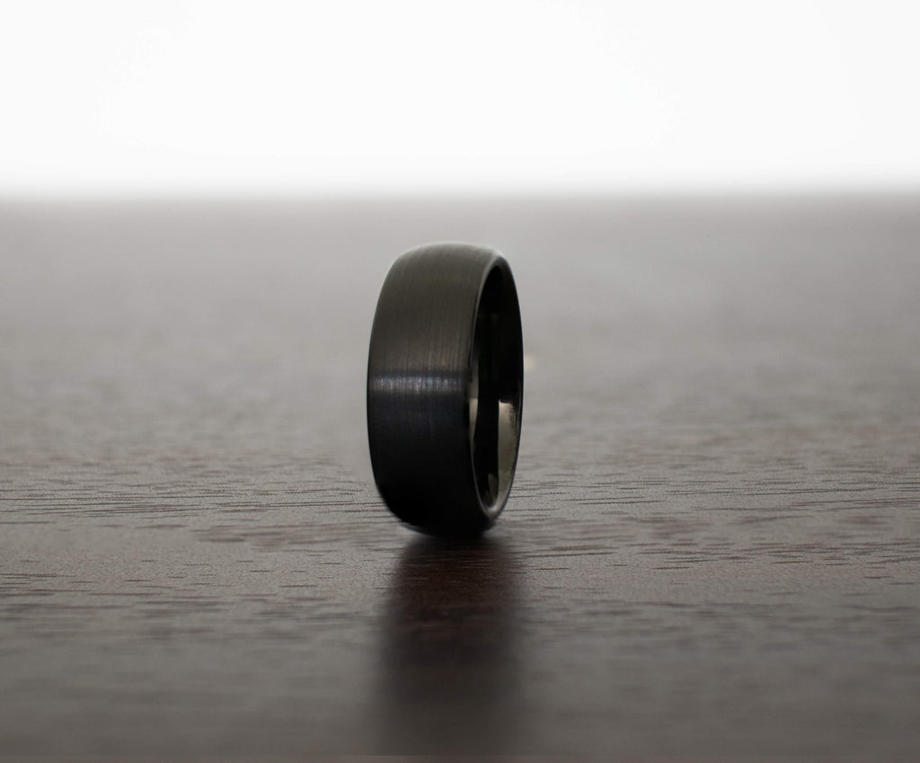 black-raven-hue-tungsten-mens-wedding-band-on-table-slight-angle