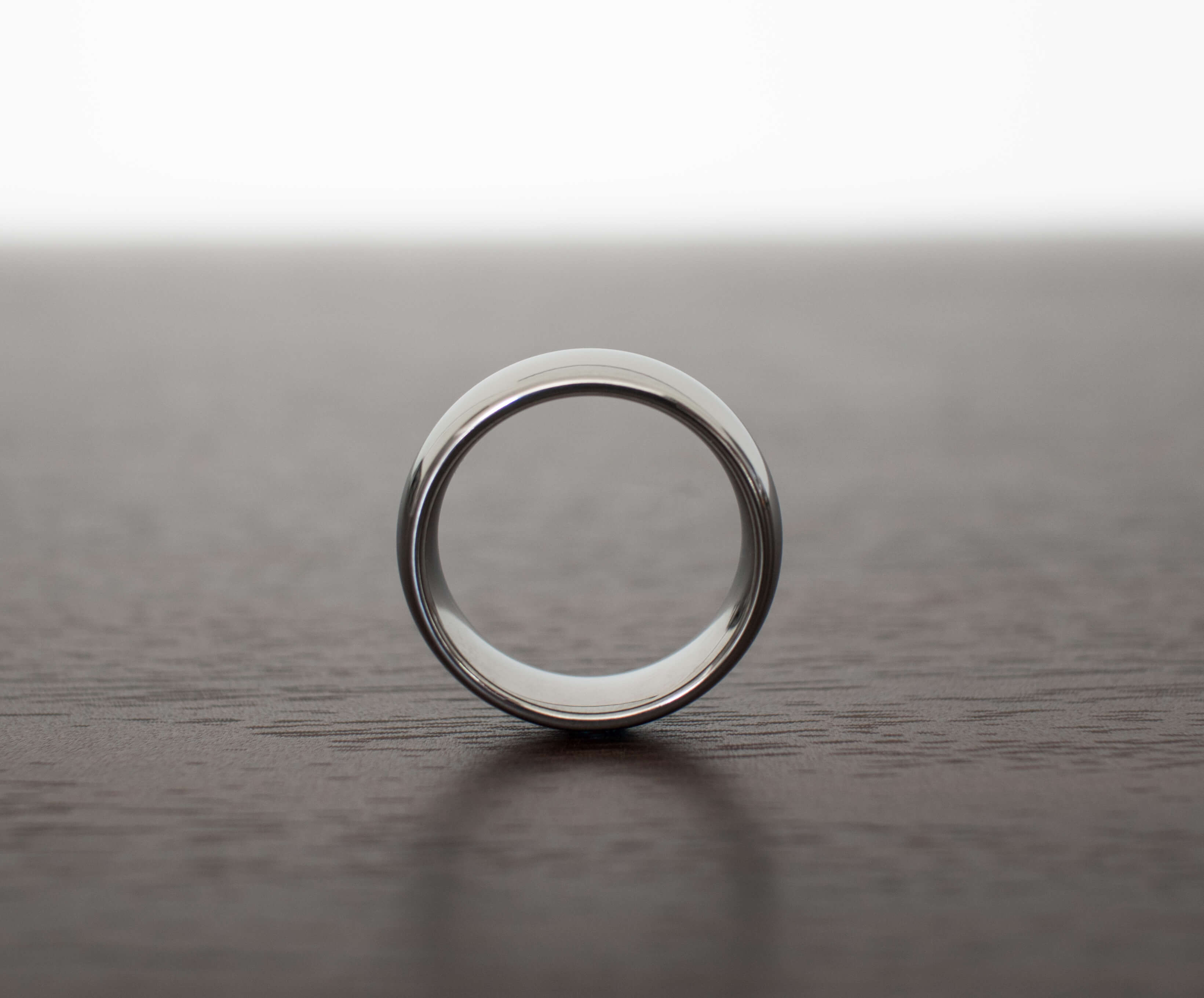 classic-silver-wedding-band-for-men-on-table-with-side-view