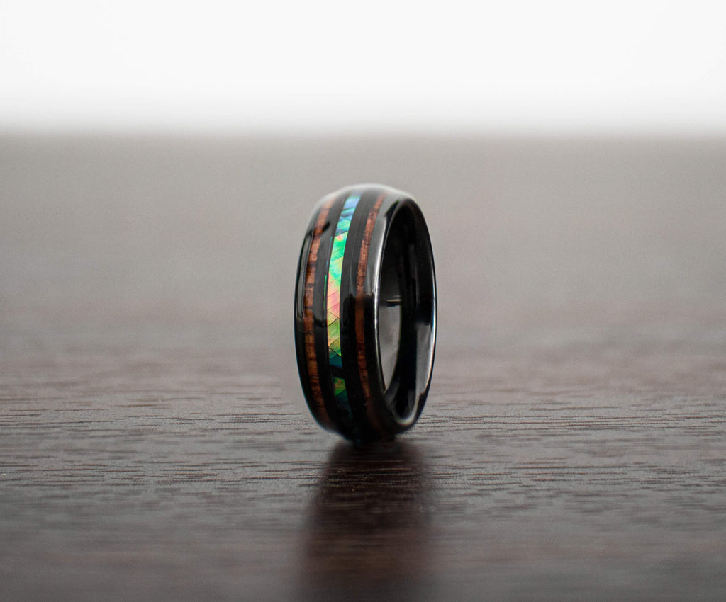 dark-elk-wood-wedding-band-on-table-with-slight-side-view