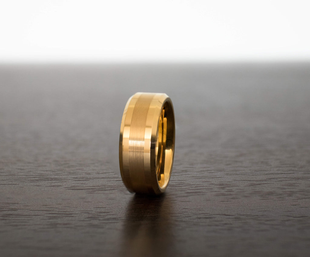 gold-center-brushed-tungsten-mens-wedding-band-on-table-with-slight-view