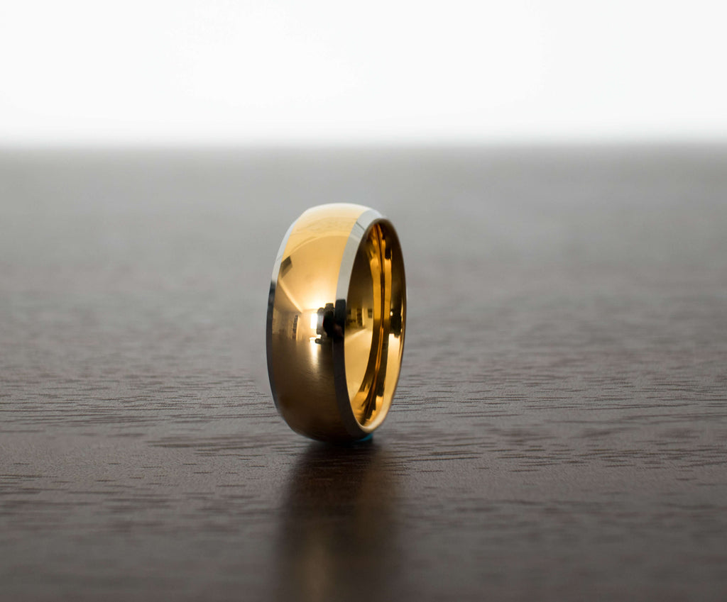 gold-elegant-silver-tungsten-mens-wedding-band-on-table-with-slight-view