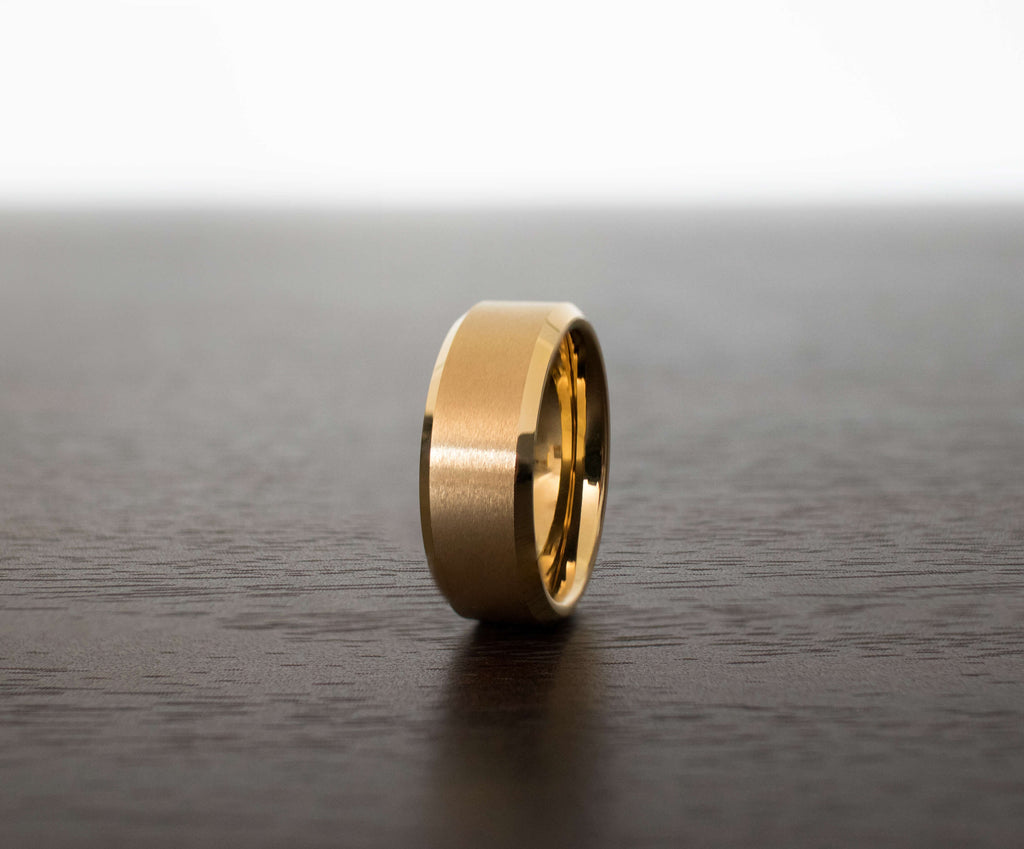 gold-full-brush-tungsten-men-wedding-band-on-table-with-slight-view