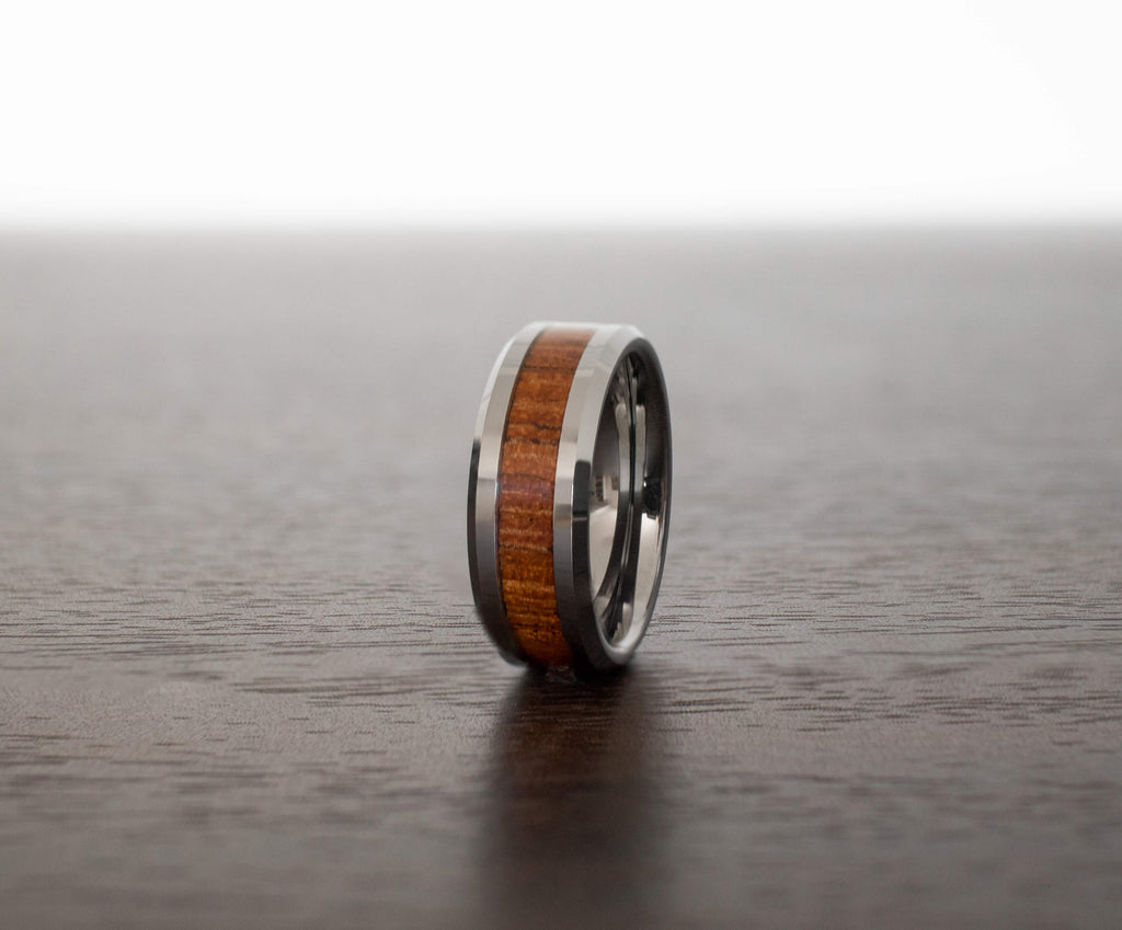 koa-wood-mens-wedding-band-in-abalone-shell-on-table-with-slight-view
