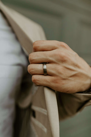 man-in-light-tan-suit-holding-jacket-out-to-show-silver-tungsten-wedding-band