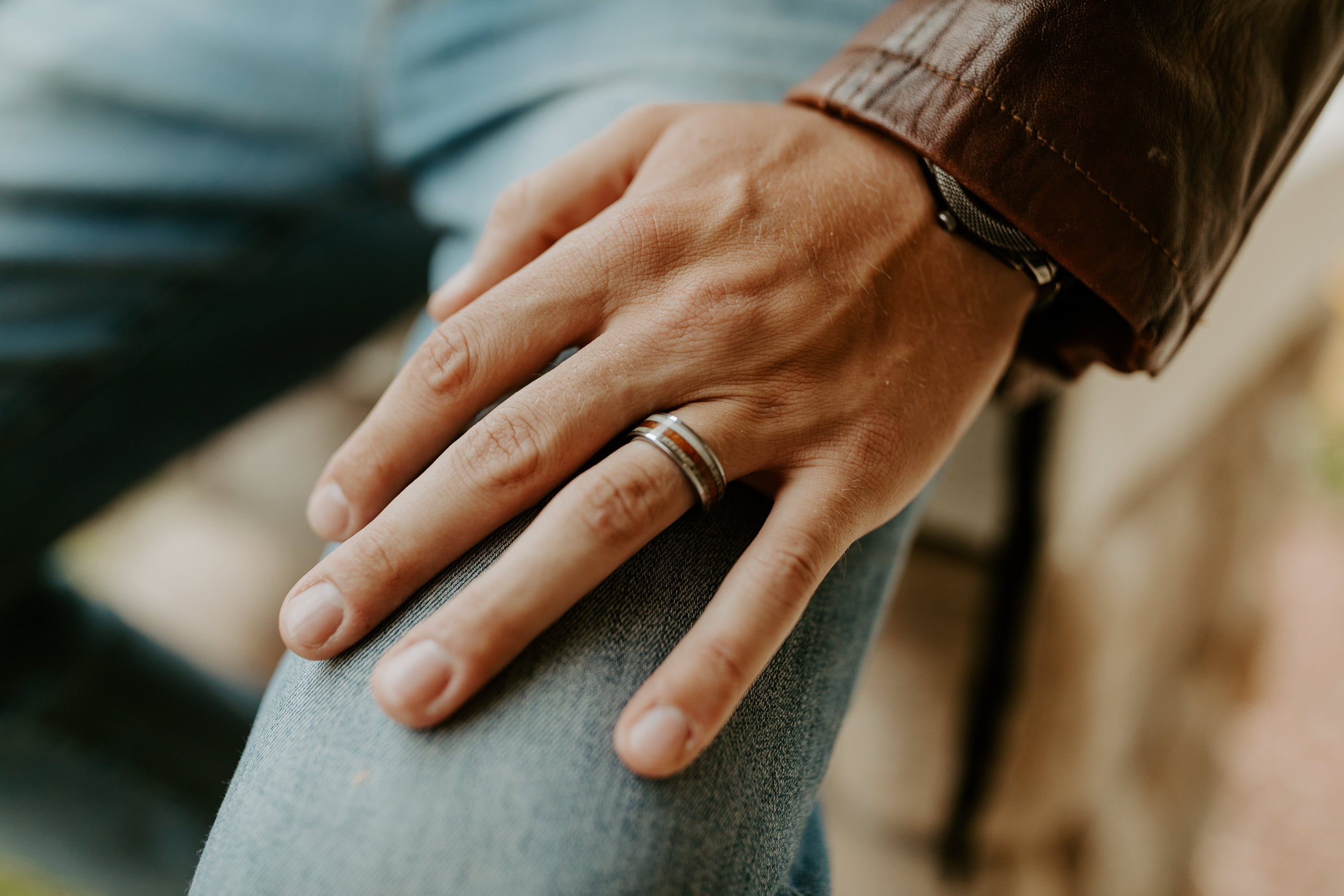 man-with-hand-on-lap-showing-mens-wedding-band-made-of-antler-wood