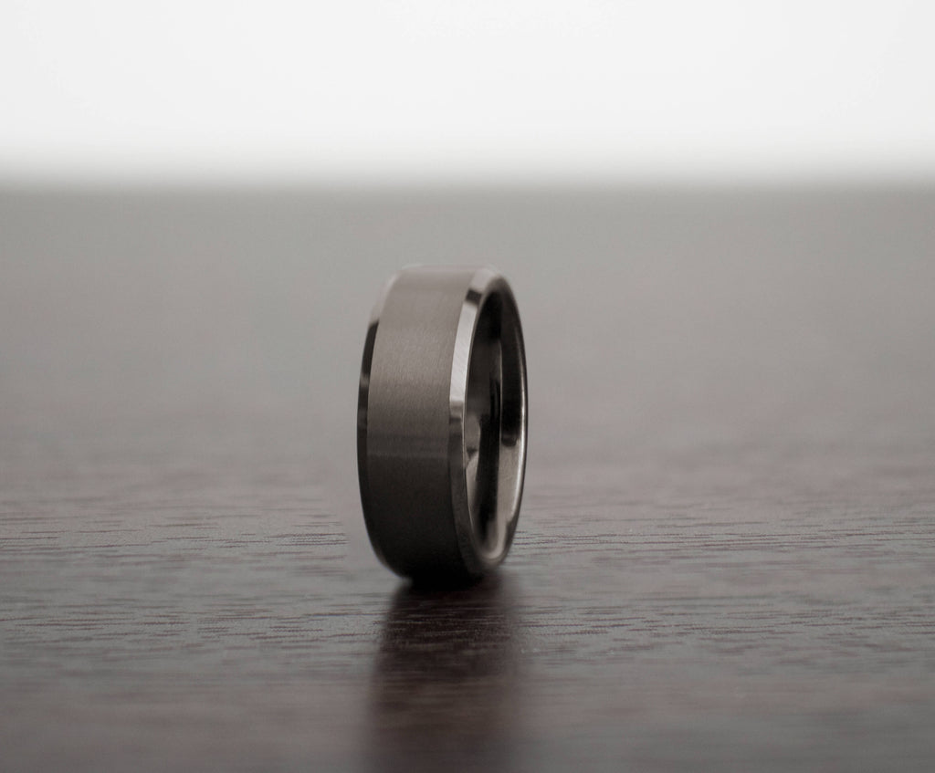 mens-gunmetal-silencer-tungsten-wedding-band-slight-angle-on-table