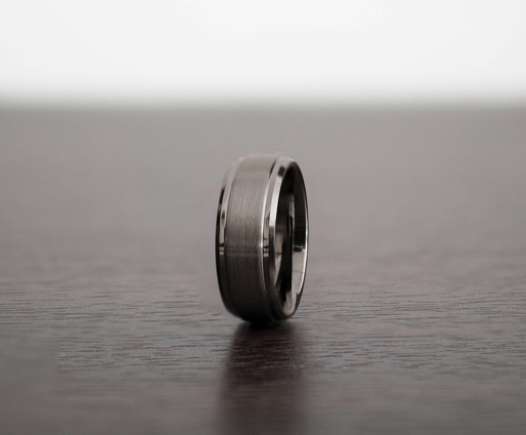 mens-gunmetal-tommy-tungsten-wedding-band-slight-angle-on-table