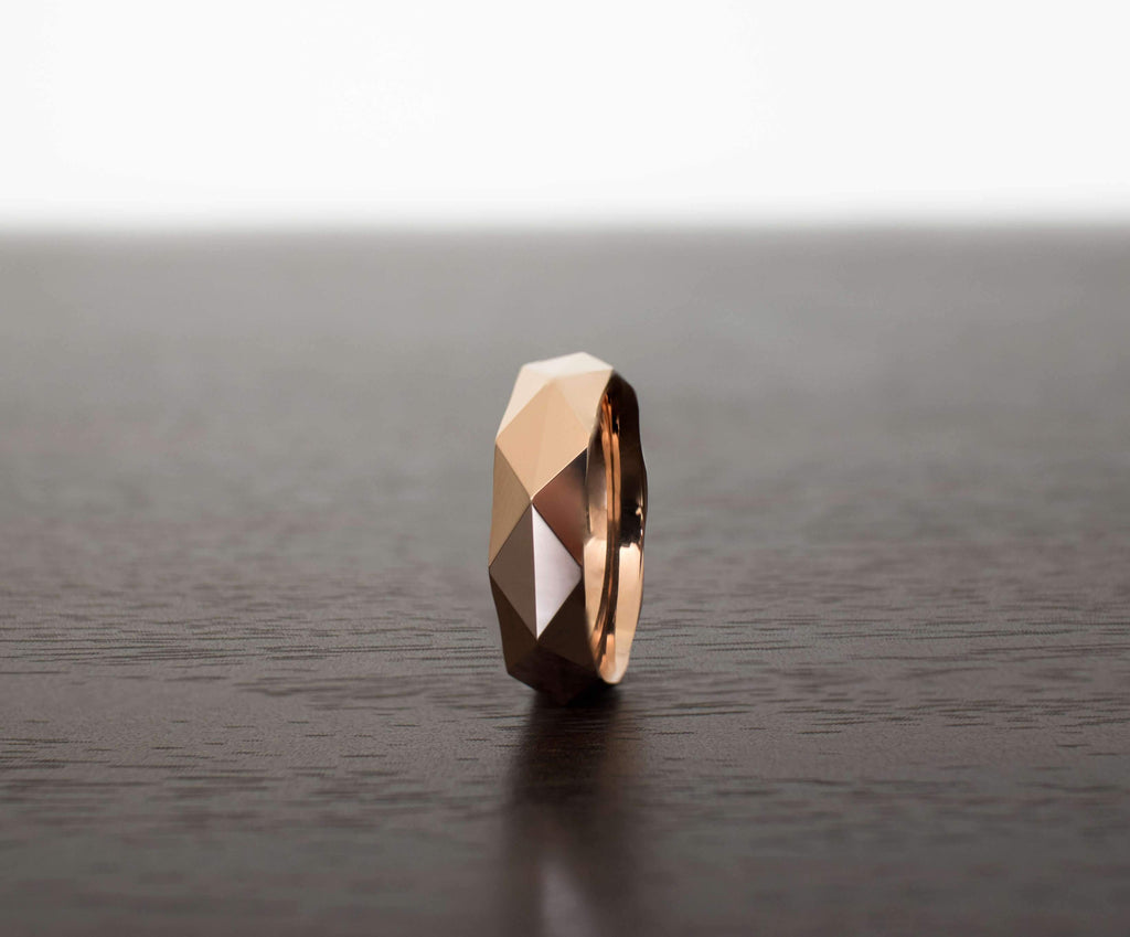 rose-gold-prism-mens-tungsten-wedding-band-on-table-with-slight-angle