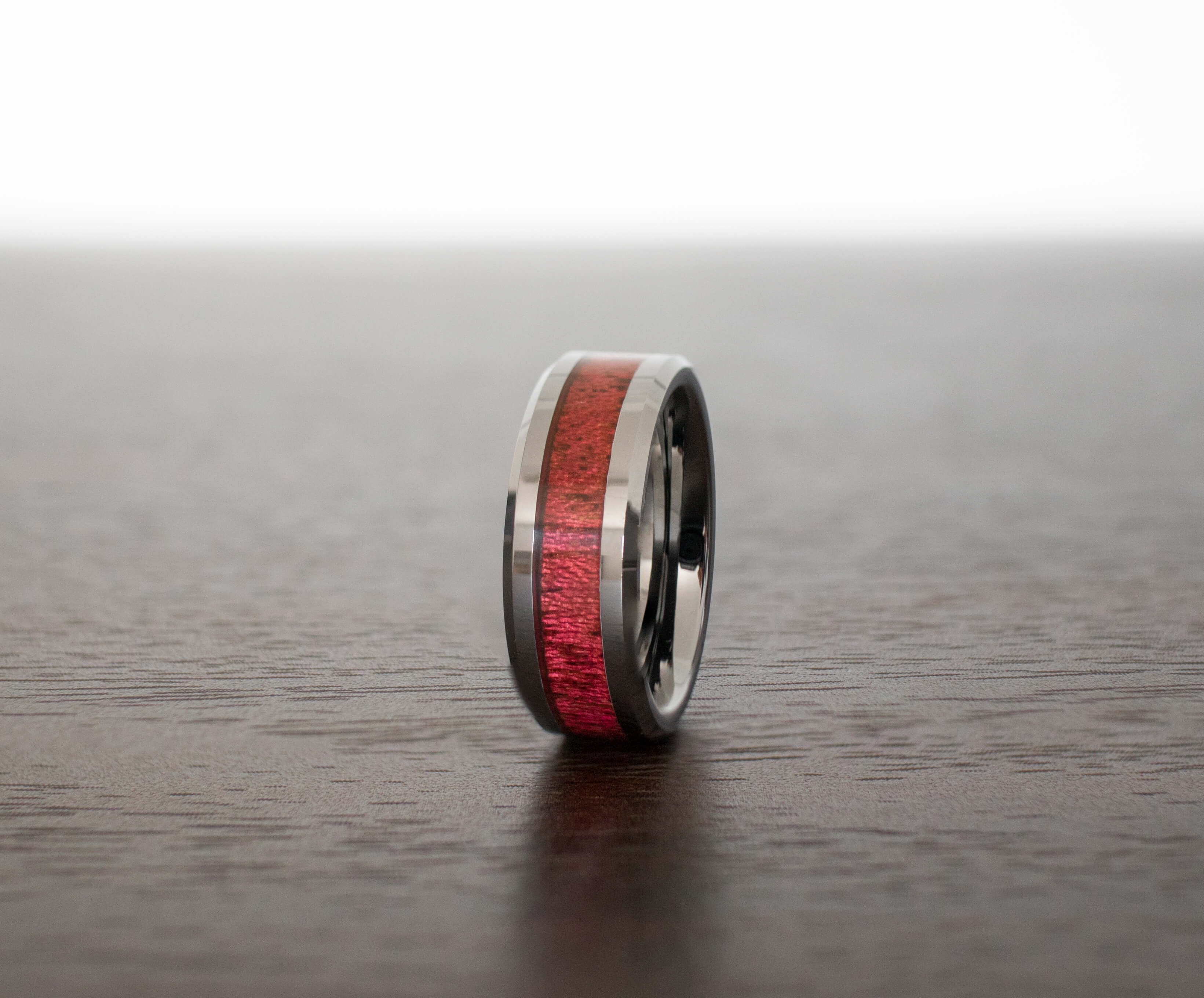 rosewood-mens-wedding-band-in-abalone-shell-on-table-with-slight-view