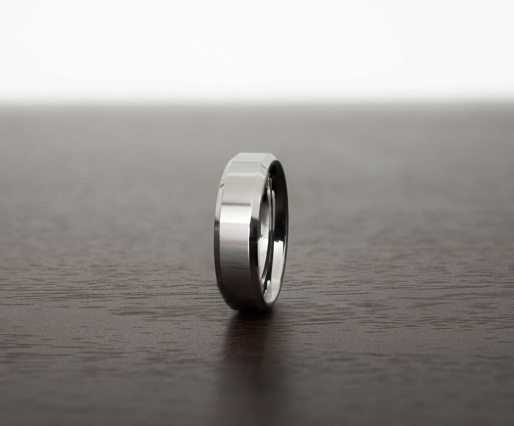 silver-obsidian-sleek-tungsten-carbide-men-wedding-band-on-table-slight-angle