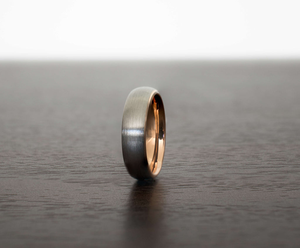 thin-silver-rose-gold-mens-tungsten-wedding-band-on-table-with-slight-angle