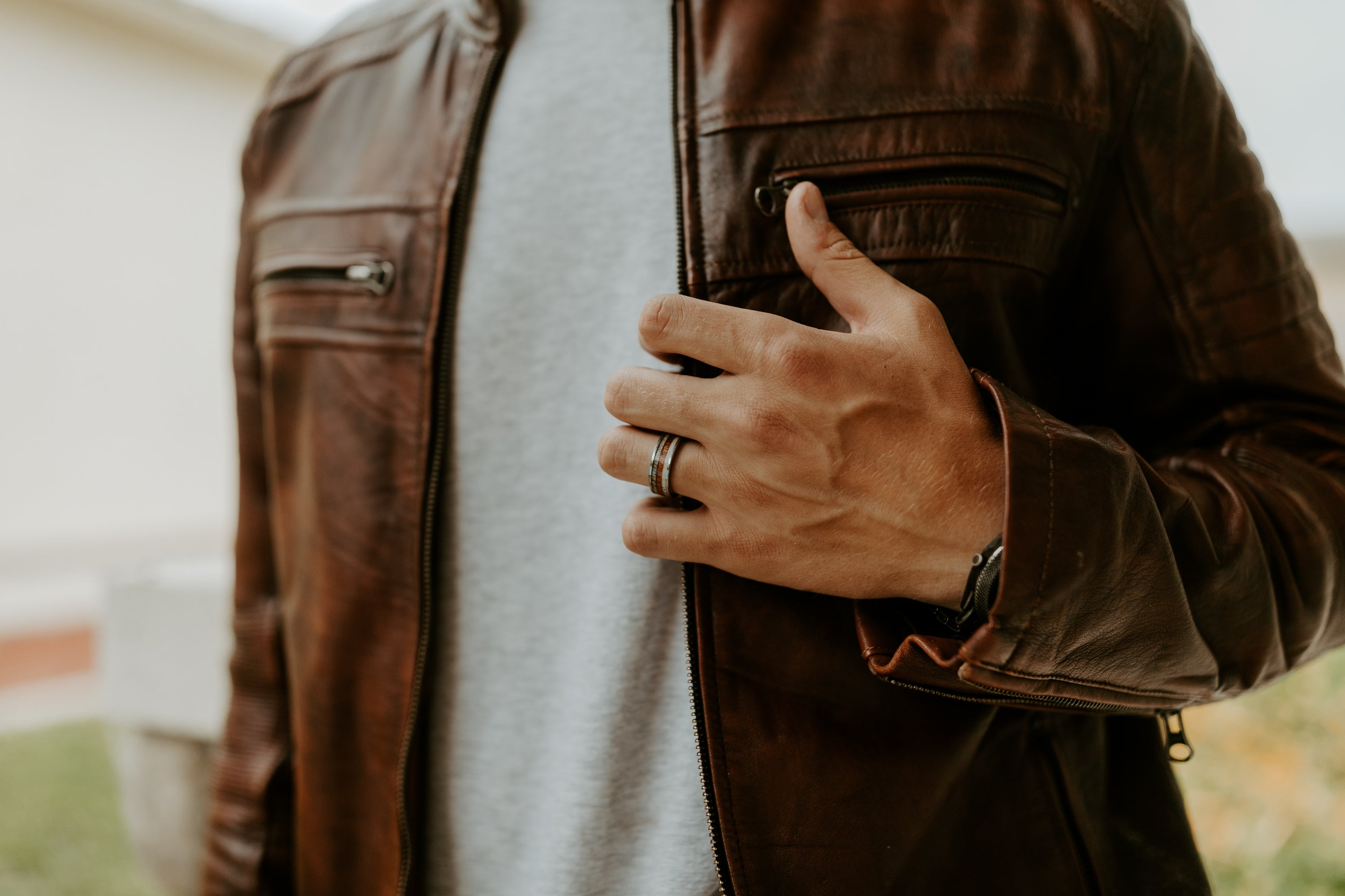 torso-view-of-man-in-leather-jacket-holding-hand-up-to-show-antler-wood-ring