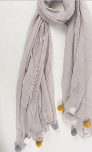 light grey scarf with large white, grey and mustard pom poms. Friday Offer