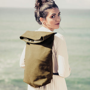 Girl with khaki green hemp backpack in the ocean