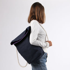 Girl in jeans with backpack in blue hemp canvas with off white rope strap