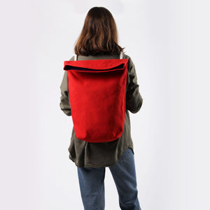 Girl in green shirt and jeans with red hemp canvas backpack