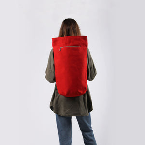 Girl in green shirt and jeans with red hemp canvas backpack with zipper detail