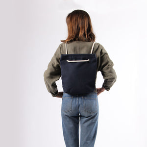 Girl in jeans with bakpack in blue hemp canvas with off white rope strap