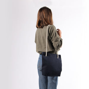 Girl in jeans with shoulder bag in blue hemp canvas with off white rope strap