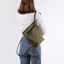 Load image into Gallery viewer, Girl in jeans with backpack in khaki green hemp canvas with black rope strap