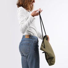 Load image into Gallery viewer, Girl in jeans turning backpack into shoulder bag
