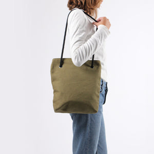Girl in jeans with shoulder bag in khaki green hemp canvas with black rope strap