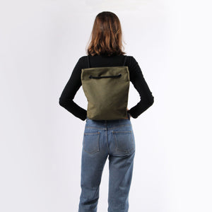 Girl in jeans with backpack in khaki green hemp canvas with black rope strap