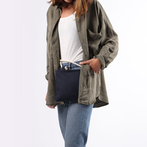 Model in jeans with Beltbag in blue hemp canvas with off white rope strap