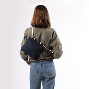 Girl in jeans with crossbody bag in blue hemp canvas with off white rope strap