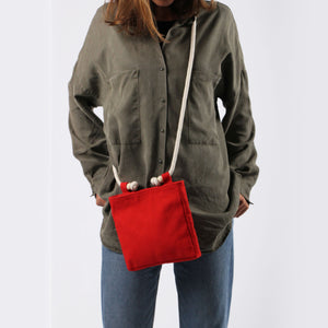 Girl in jeans with crossbody in red hemp canvas with off white rope strap