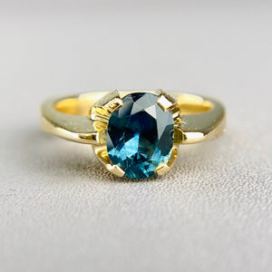 Green-blue sapphire solitaire in yellow gold