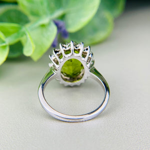 Large oval peridot and diamond halo cluster ring