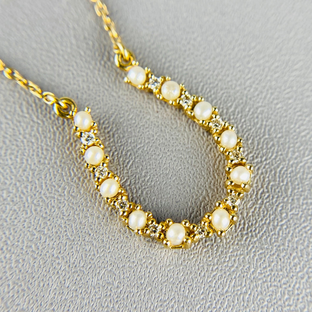Pearl and diamond horseshoe necklace in 14k yellow gold