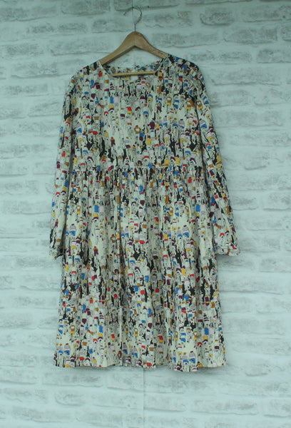 Dress hanging on white brick background.  All over cycle print. Lithuanian Cotton