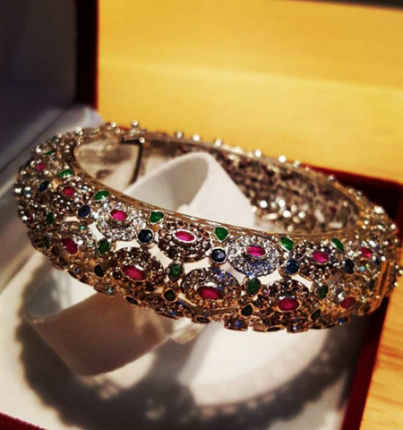 Sterling silver bangle bracelet by Amna's Inspiration with rubies, emeralds and sapphires.