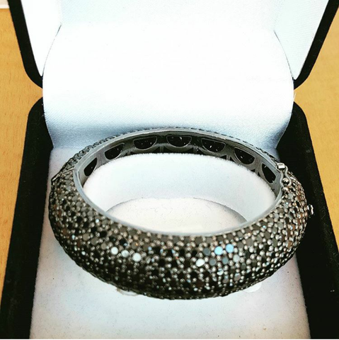 Sterling silver bangle bracelet by Amna's Inspiration with sapphires.
