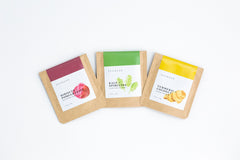 image of three SCHMEAR face mask packets in kraft brown envelopes with pink, green, and yellow labels