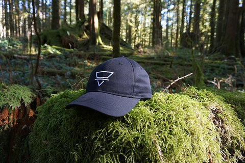 image of black Ardor and Wild Earth hat on mossy rock with a sunny forest in the background