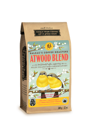 kraft brown bag of coffee with label featuring teal blue background, and two yellow birds sitting on budding tree branches