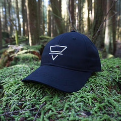 black ball cap with white alchemic sign for earth (inverted triangle with horizontal line through middle), sitting on mossy rock in a sunlit forest