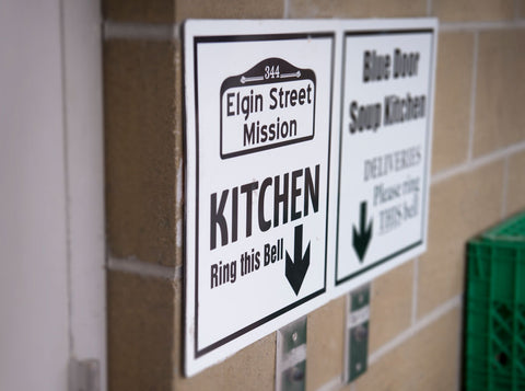 image of Elgin Street Mission logo on white sign on brick wall near doorbell for the back door of The Mission