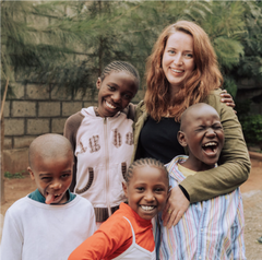 image of ZLT founder, Jacqueline Villeneuve, standing with four of the ZLT children who are making silly faces