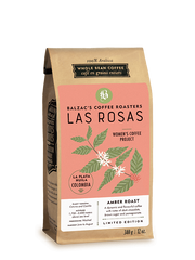bag of Las Rosas coffee; brown kraft bag with coral label featuring a plant with green leaves, white flowers, and red berries