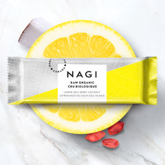 image of NAGI lemon goji bar sitting atop a halved lemon with a piece of coconut to the top left and three goji berries to the bottom right; all against a white marble background