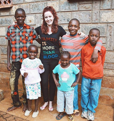 image of ZLT founder, Jacqueline Villeneuve, wearing shirt that reads 'family is more than blood', standing outside the ZLT home with five of the children