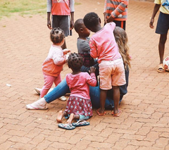 image of Jacqueline sitting on brick walkway, surrounded by ZLT children who are playing with her hair