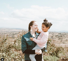 image of ZLT founder, Jacqueline, standing outside in Kenya, holding child in her arms